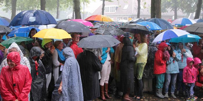 Schuilen onder de paraplu tijdens regenbui opening Muziek aan de Middenweg 2016